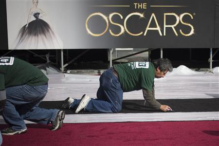 A man makes preparations along the red carpet on Hollywood Boulevard, ahead of the 85th Academy Awards in Los Angeles, California February 21, 2013. REUTERS/Adrees Latif