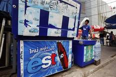 A man carries a bag with ice past a cooler with an advertisement for est sodas in Bangkok January 29, 2013. REUTERS/Kerek Wongsa
