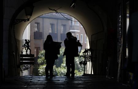 Tourists refer to a map as they walk through Plaza Mayor in central Madrid February 5, 2013. REUTERS/Sergio Perez