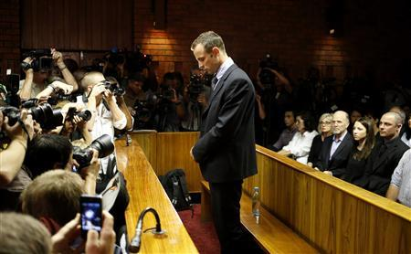 Oscar Pistorius stands at the dock before the start of proceedings at a Pretoria magistrates court February 22, 2013. ''Blade Runner'' Pistorius, a double amputee who became one of the biggest names in world athletics, was applying for bail after being charged in court with shooting dead his