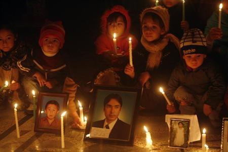 Shi'ite Muslims hold lighted candles at the site of Saturday's bomb attack, to mourn for the victims, in Quetta February 21, 2013. REUTERS/Naseer Ahmed