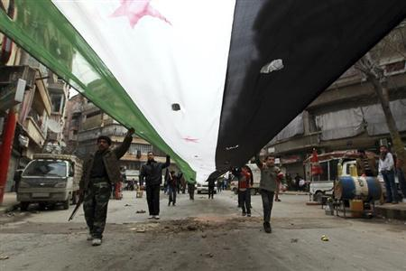 Demonstrators hold a giant opposition flag during a protest against Syria's President Bashar al-Assad in Bustan al-Qasr district in Aleppo February 22, 2013. REUTERS/Muzaffar Salman