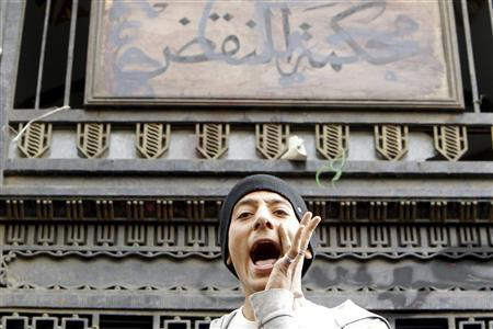 A protester shouts in front of the sign for the court of cassation during an anti-government protest in Cairo February 22, 2013. President Mohamed Mursi on Thursday called parliamentary elections that will begin on April 27 and finish in late June, a four-stage vote that the Islamist leader hopes will conclude Egypt's turbulent transition to democracy. REUTERS/Mohamed Abd El Ghany