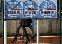 Donne camminano dietro manifesti elettorali di Berlusconi in vista delle elezioni politiche del 24 e 25 febbraio. Napoli, 22 febbraio 2013. REUTERS/Alessandro Bianchi