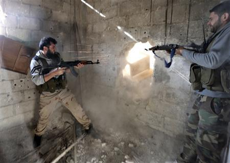 Fighters from the Free Syrian Army's Tahrir al Sham brigade fire back at the Syrian army during heavy fighting in Mleha suburb of Damascus, in this January 26, 2013 file photo. REUTERS/Goran Tomasevic/Files