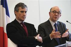 Le ministre de l'Economie et des Finances Pierre Moscovici et son collègue du Budget Jérôme Cahuzac, à Paris. La France va entamer des discussions avec la Commission européenne pour obtenir un report à 2014 de l'objectif des 3% de baisse des déficits publics sur lequel elle s'était engagée pour 2013, après une forte révision en baisse de ses perspectives économiques. /Photo prise le 22 février 2013/REUTERS/Philippe Wojazer