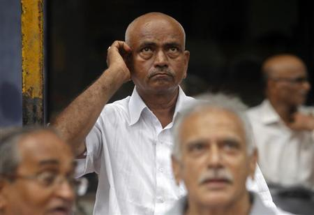 An investor scratches his head as he looks at a display of stock prices outside the Bombay Stock Exchange (BSE) building in Mumbai June 18, 2012. REUTERS/Vivek Prakash/Files