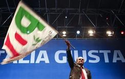 Il leader del Pd Pier Luigi Bersani sventola la bandiera del suo partito a Napoli, 21 febbraio 2013. REUTERS/Ciro De Luca