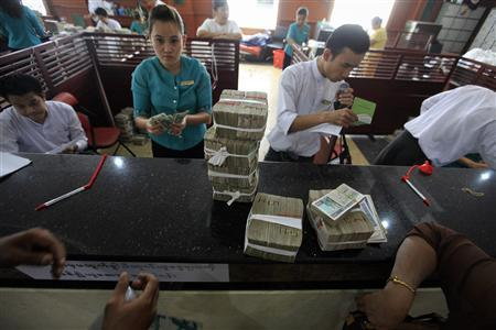 People exchange currency to Myanmar's kyat banknotes at the office of a local bank in Yangon April 2, 2012. REUTERS/Soe Zeya Tun