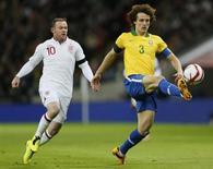 David Luiz (D) disputa lance em amistoso da seleção brasileira contra a Inglaterra, em 6 de fevereiro. O zagueiro disse que está pronto para jogar no meio-campo, se for preciso. REUTERS/Stefan Wermuth
