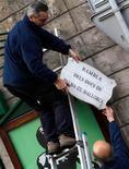 El yerno del Rey de España, Iñaki Urdangarin, comparece el sábado ante el juez para responder a las nuevas acusaciones que pesan contra él por usar presuntamente su posición como esposo de la infanta Cristina para delinquir contra la Hacienda Pública con el fin de enriquecerse. En la imagen, trabajadores retiran la placa de una calle con el título de la infanta Cristina y su marido, Iñaki Urdangarin, en Palma de Mallorca, el 8 de febrero de 2013. REUTERS/Enrique Calvo