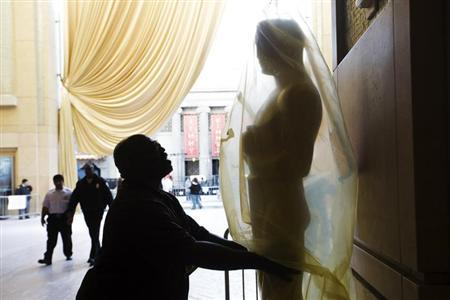 A worker places an Oscar statue on the red carpet during preparations for the 85th Academy Awards in Hollywood, California, February 21, 2013. REUTERS/Lucas Jackson