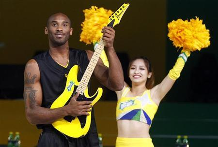 NBA basketball player Kobe Bryant of the U.S. poses with an electric guitar during a charity basketball game in Shanghai August 18, 2012. REUTERS/Carlos Barria