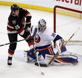 New York Islanders goalie Rick DiPietro (R) makes a save against Ottawa Senators Chris Neil during the second period of their NHL hockey game in Ottawa February 19, 2013. REUTERS/Chris Wattie