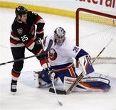 New York Islanders goalie Rick DiPietro (R) makes a save against Ottawa Senators Chris Neil during the second period of their NHL hockey game in Ottawa February 19, 2013. REUTERS/Chris Wattie