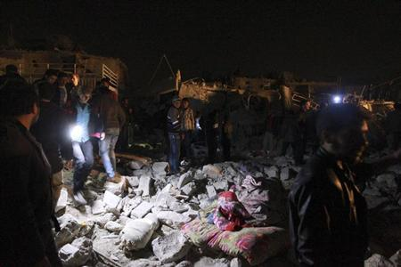 People gather to search for survivors after what activists said was a Scud missile hit in Aleppo's Tariq al-Bab neighbourhood February 22, 2013. REUTERS/Muzaffar Salman
