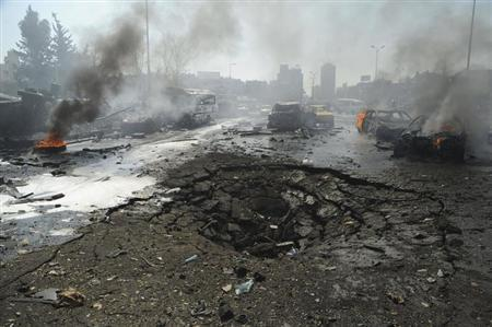 Vehicles burn near a crater on a road after an explosion at central Damascus February 21, 2013, in this handout photograph released by Syria's national news agency SANA. REUTERS/Sana (ATTENTION EDITORS - THIS PICTURE WAS PROVIDED BY A THIRD PARTY. REUTERS IS UNABLE TO INDEPENDENTLY VERIFY THE AUTHENTICITY, CONTENT, LOCATION OR DATE OF THIS IMAGE. FOR EDITORIAL USE ONLY. NOT FOR SALE FOR MARKETING OR ADVERTISING CAMPAIGNS. THIS PICTURE IS DISTRIBUTED EXACTLY AS RECEIVED BY REUTERS, AS A SERVICE TO CLIENTS)