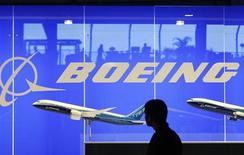 A man looks at a scale model of Boeing's 787 dreamliner at their booth at the Singapore Air Show in Singapore February 19, 2008. REUTERS/Vivek Prakash