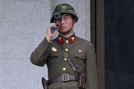 A North Korean soldier looks south through a pair of binoculars on the north side of the truce village of Panmunjom in the demilitarised zone separating the two Koreas in Paju, about 55 km (34 miles) north of Seoul, August 25, 2010. REUTERS/Jo Yong-Hak