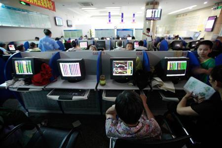 Investors look at computer screens showing stock information at a brokerage house in Shanghai July 30, 2012. REUTERS/Aly Song