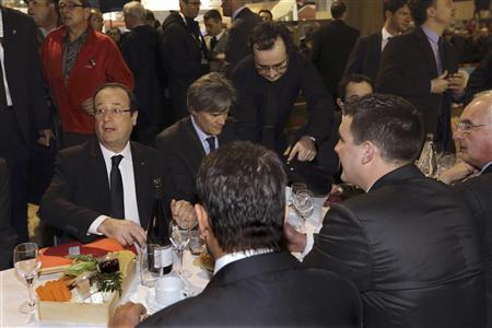 French President Francois Hollande (L) shares a breakfast with farmers during his visit at the 50th International Agricultural Show in Paris, February 23, 2013. The Paris Farm Show runs from February 23 to March 3, 2013. REUTERS/Philippe Wojazer