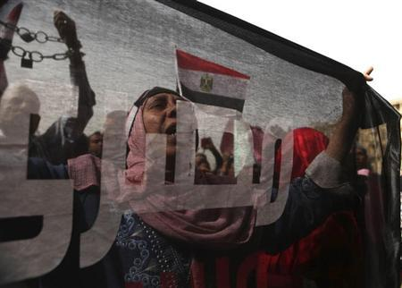 A protester who opposes Egyptian President Mohamed Mursi, is seen through a flag, on which the word ''Egyptian'' is inscribed, as she chants slogans during a demonstration against Mursi and members of the Muslim Brotherhood at Tahrir Square in Cairo February 22, 2013. Egyptian parliamentary elections will begin on April 27 and finish in late June, in a four-stage vote. REUTERS/Asmaa Waguih (EGYPT - Tags: POLITICS CIVIL UNREST TPX IMAGES OF THE DAY)