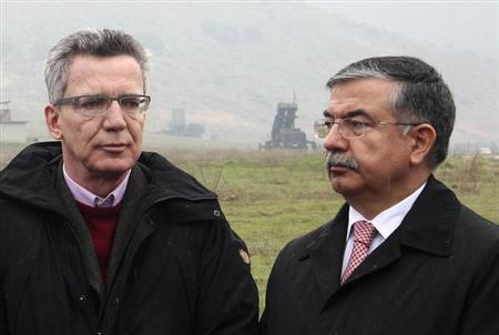 Germany's Minister of Defense Thomas de Maiziere (L) and his Turkish counterpart Ismet Yilmaz, with the Patriot system in the background, are seen during their visit NATO German patriot troops at a Turkish military base in Kahramanmaras February 23, 2013. REUTERS/Stringer (TURKEY - Tags: POLITICS MILITARY)