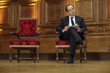 French President Francois Hollande holds his notes as he attends a conference on ''Civil servants in Dictatorial Europe'' at the Sorbonne in Paris February 21, 2013. REUTERS/Philippe Wojazer