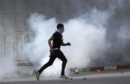 A Palestinian protester runs past tear gas during clashes with Israeli security forces in the West Bank city of Hebron February 22, 2013. Israeli forces clashed with Palestinian protesters throughout the occupied West Bank on Friday, capping a week of violence amid a hunger strike by four Palestinians in Israeli jails. REUTERS/Darren Whiteside