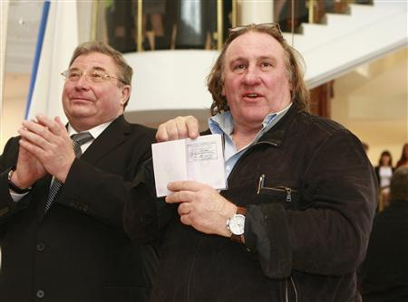 French film star Gerard Depardieu (R) shows his passport with residency permit as Vladimir Volkov, head of the Republic of Mordovia, applauds during a visit to the town of Saransk, southeast of Moscow February 23, 2013. REUTERS/Yulia Chestnova