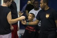 Downey Christian high school varsity basketball player 11-year-old Julian Newman (C) greets other participants during Friday evening pickup basketball games at Downey Christian School in Orlando, Florida February 22, 2013. At 4 feet 5 inches tall, starting point guard Julian Newman stands waist high next to other players on his Florida high school basketball team. But his talent towers over the competition. At only 11, Newman leads the state of Florida in assists per game this season and ranks fifth nationally, according to Maxpreps.com, which maintains statistics on high school sports. REUTERS/Scott Audette