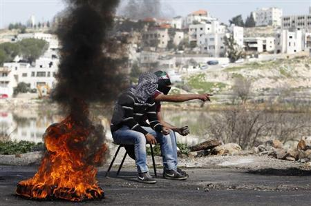 Palestinians hold stones as they sit next to a burning tyre during clashes with Israeli troops outside Israel's Ofer military prison near the West Bank city of Ramallah February 21, 2013. REUTERS/Darren Whiteside