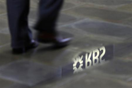 A man walks past a Royal Bank of Scotland branch reflected in a puddle in central London January 14, 2010. REUTERS/Stefan Wermuth