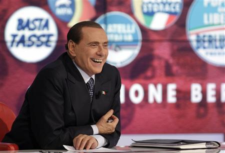 Italy's former Prime Minister Silvio Berlusconi smiles as he appears as a guest on the RAI television show Porta a Porta (Door to Door) in Rome February 22, 2013. REUTERS/Remo Casilli