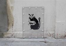 A rat is painted next to a section of wall that was removed and shipped to the U.S., in north London February 23, 2013. The section that was removed had a painting on it's surface, thought to be by graffiti artist Banksy. The work, known as 'SlaveLabour', and the piece of wall it was painted on, is up for sale at a Miami auction house. REUTERS/Neil Hall