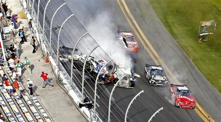 NASCAR driver Kyle Larson (32) and his Chevrolet end up in the fence during the final lap crash during the during the NASCAR Nationwide Series 32nd Annual DRIVE4COPD 300 at the Daytona International Speedway in Daytona Beach, Florida February 23, 2013. REUTERS/Pierre Ducharme