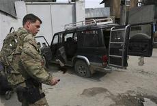 A U.S, soldier from International Security Assistance Force (ISAF) is seen next to a vehicle used by an insurgent, who was killed by security forces in Kabul February 24, 2013. Afghan intelligence officers shot dead at least one would-be suicide bomber in Kabul's most well-protected area home to some of the country's most high-profile targets, Kabul police said on Sunday. REUTERS/Omar Sobhani