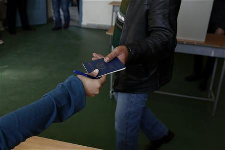 A man is handed his voting documents as he leaves a polling station in Limassol February 24, 2013. REUTERS/Yorgos Karahalis