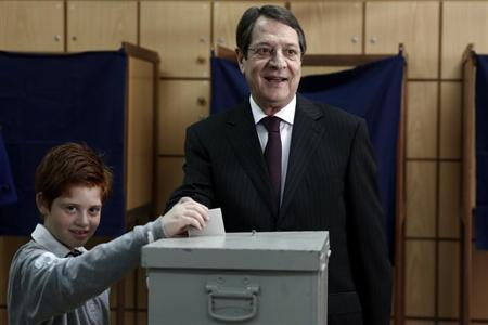 Cyprus presidential candidate Nicos Anastasiades of the right wing Democratic Rally party (R) casts his ballot with his grandson Andis at a polling station in Limassol February 24, 2013. Cypriots started voting in a runoff on Sunday to elect a president who must clinch a bailout deal for the island nation to avoid a financial meltdown that would revive the euro zone crisis. Conservative leader Anastasiades, who favors hammering out a quick deal with foreign lenders, is favored to win against Communist-backed rival Stavros Malas, who is more wary of the austerity terms accompanying any rescue. REUTERS/Yorgos Karahalis (CYPRUS - Tags: POLITICS ELECTIONS)