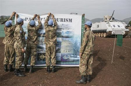 United Nations peacekeepers put up a sign about tourism in Pakistan as they prepare for the global rally ''One Billion Rising'', which is part of a V-Day event calling for an end to gender-based violence, in Bukavu February 14, 2013. V-Day is a global activist movement to end violence against women and girls. REUTERS/Jana Asenbrennerova (DEMOCRATIC REPUBLIC OF THE CONGO - Tags: SOCIETY CIVIL UNREST)