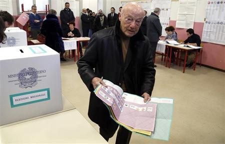 A man holds election ballots before casting his vote at the polling station in Milan, February 24, 2013. REUTERS/Stefano Rellandini