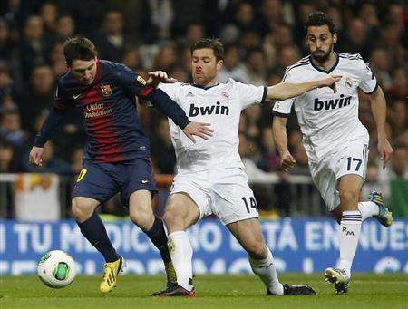 Barcelona's Lionel Messi (L) is challenged by Real Madrid's Xabi Alonso and Alvaro Arbeloa (R) during their Spanish King's Cup semi final first leg soccer match at Santiago Bernabeu stadium in Madrid January 30, 2013. REUTERS/Sergio Perez