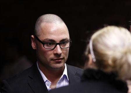 Carl Pistorius, brother of South African ''Blade Runner'' Oscar Pistorius, speaks with an unidentified person ahead of his brothers court appearance in Pretoria February 15, 2013. REUTERS/Siphiwe Sibeko
