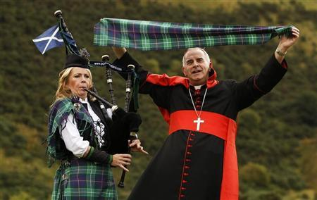 Cardinal Keith O?Brien poses with the worlds first Papal Visit plaid, next to piper Louise Millington, in Edinburgh, Scotland September 9, 2010. REUTERS/David Moir