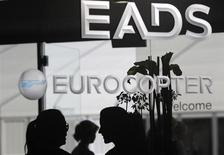Visitors talk near the welcome desk of the EADS booth at the ILA Berlin Air Show in Selchow near Schoenefeld south of Berlin on September 13, 2012. REUTERS/Tobias Schwarz (