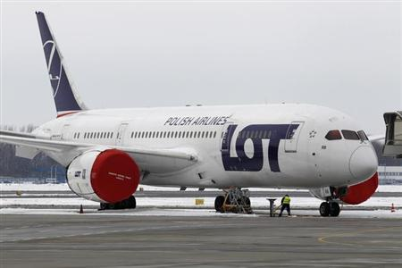 A Dreamliner belonging to Polish airline LOT is being parked on the tarmac at Chopin International Airport in Warsaw February 13, 2013. Poland's national airline LOT will not use its Boeing Dreamliner passenger jets before October, LOT's chief executive said on February 14, 2013. The airline said earlier it would seek compensation from Boeing after most of the U.S. planemaker's 787 Dreamliner passenger jets were grounded due to battery-related problems. Picture taken February 13, 2013. REUTERS/Peter Andrews (POLAND - Tags: TRANSPORT BUSINESS)