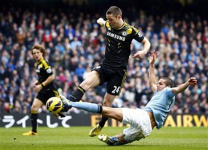 Manchester City's Jack Rodwell (R) challenges Chelsea's Gary Cahill during their English Premier League soccer match at The Etihad Stadium in Manchester, northern England, February 24, 2013. REUTERS/Darren Staples