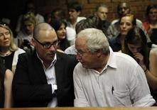 """El hermano mayor de Oscar Pistorius se enfrenta a un juicio por causar la muerte de una mujer en un accidente de tráfico hace cinco años, dijo el domingo la familia, confirmando una publicación que dominó los medios sudafricanos dos días después de que el atleta apodado """"Blade Runner"""" recibiera la libertad bajo fianza por asesinato. En la imagen, de 20 de febrero, el hermano de Oscar Pistorius, Carl Pistorius con su padre durante el juicio por la muerte de su novia. REUTERS/Siphiwe Sibeko"""