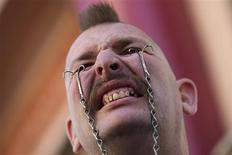 Performance artist George the Giant attaches hooks into his eyelids to hold a soda bottle ahead of the sixth annual World Sword Swallower's Day celebrations outside the Ripley's Believe It or Not! museum in Los Angeles, California February 23, 2013. REUTERS/Adrees Latif