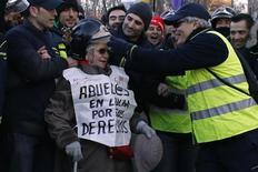 """Bombeiro coloca seu capacete em uma mulher durante protestos contra austeridade próximo ao Parlamento espanhol em Madri, Espanha. No colete da mulher, lê-se: """"Avós na luta pelos seus direitos"""". A polícia espanhola prendeu 45 pessoas após protestos no sábado que reuniram milhares de pessoas contra as medidas de austeridades e supostos atos de corrupção no governo. 23/02/2013 REUTERS/Juan Medina"""